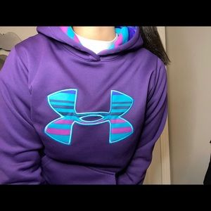 Purple under armor with colorful hoodie and sign.